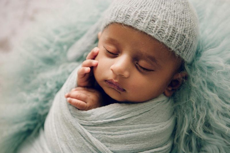 Newborn Photography of a Baby boy wrapped and sleeping on his back photographed by Victoria Burcusel