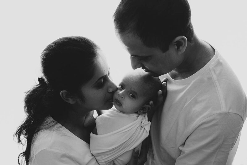 Black and white image of a newborn with his parents by Lifetime Stories Photography South Brisbane Maternity and Newborn Photographer