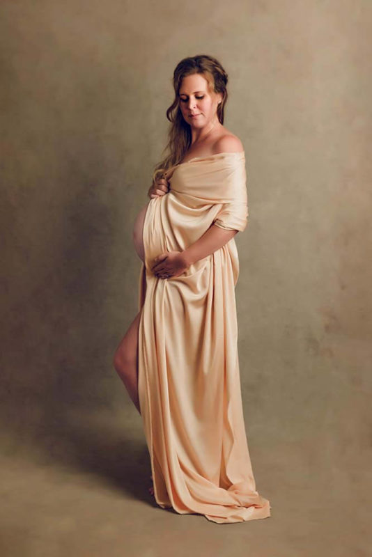 Expecting mum photographed with a golden material wrapped around her shoulder and pregnant belly photographed on hand painted golden backdrop backdrop with high key light in Brisbane South by Lifetime Stories Photography