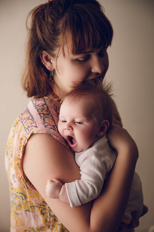 Mum holding her newborn baby on her chest and baby is yawning image by Lifetime Stories Photography