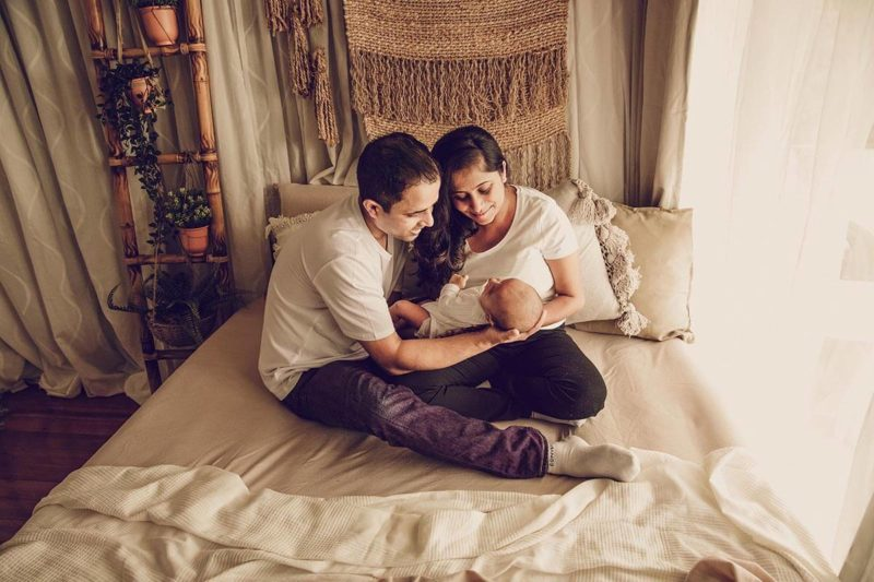 Parents holding their newborn baby in a newborn lifestyle sessions done by Lifetime Stories Photography in Rochedale South Photography Studio
