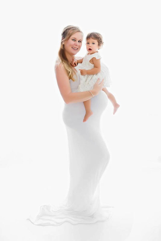 Backlit portrait of a pregnant mum holding her two years old daughter on her belly photographed by Victoria Burcusel in her home studio in Logan South Brisbane
