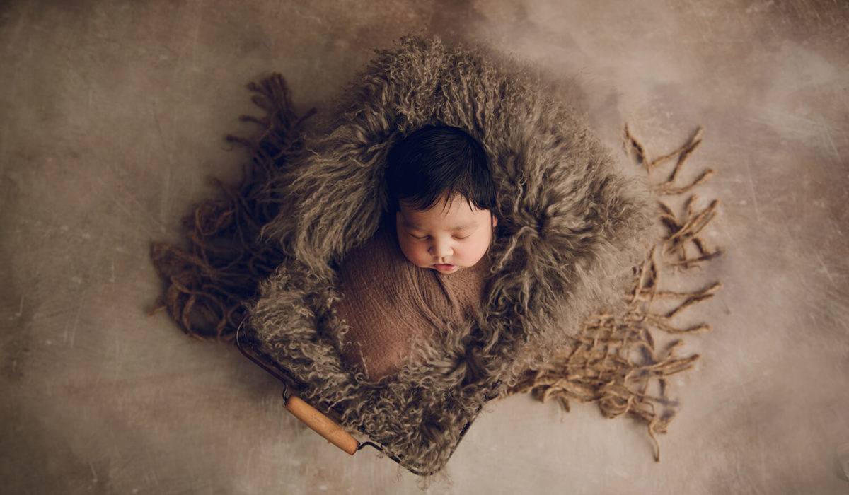 a beautiful newborn baby with lots of hair placed in a crate on his back over some brown wool curls